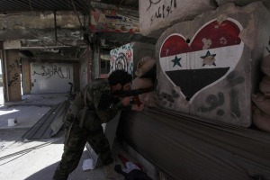 A security member loyal to Syria's President Assad holds a weapon as he takes up position in Damascus